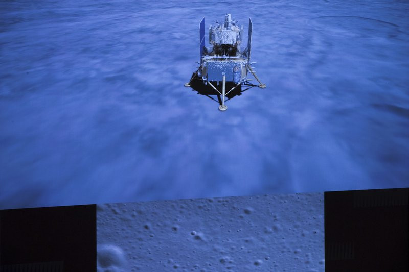 In this photo released by Xinhua News Agency, a screen shows the landed Chang'e-5 spacecraft and a moon surface picture, below, taken by camera aboard Chang'e-5 spacecraft during its landing process.