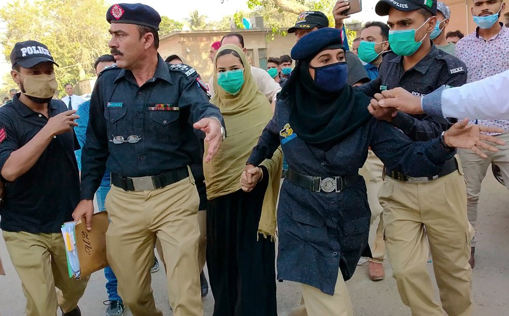 Police officers escort Arzoo Raja, background center, after her appearance in Sindh High Court, in Karachi, Pakistan, on Nov. 3, 2020.