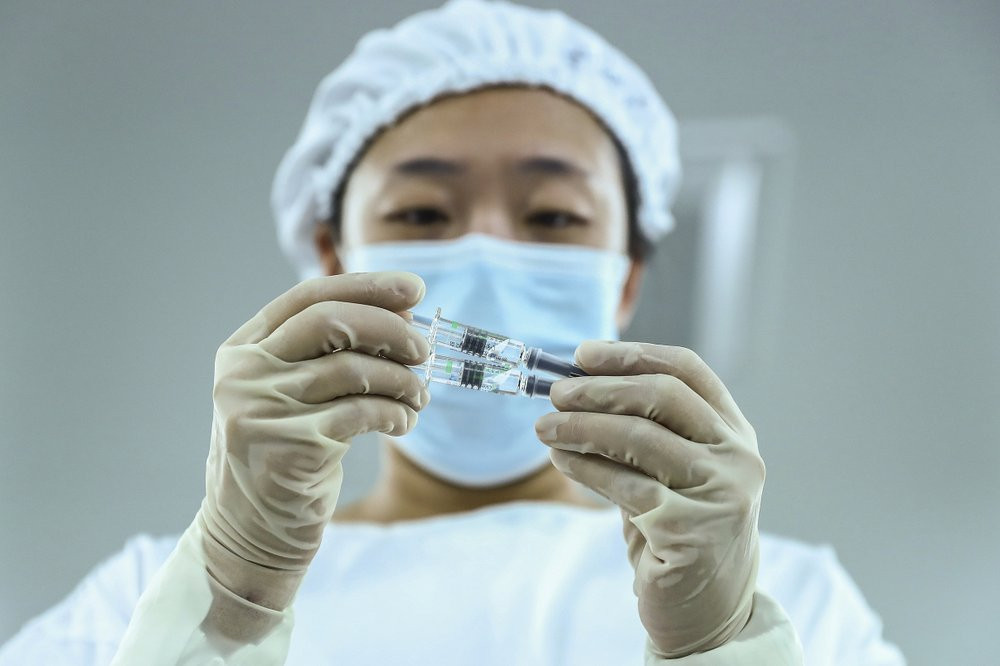 In this Dec. 25, 2020 file photo, a staff member inspects syringes of COVID-19 inactivated vaccine products at a packaging plant of the Beijing Biological Products Institute Co., Ltd, a unit of state-owned Sinopharm in Beijing.
