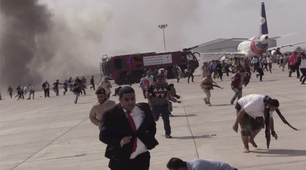 People run following an explosion at the airport in Aden, Yemen, shortly after a plane carrying the newly formed Cabinet landed on Wednesday, Dec. 30, 2020. No one on board the government plane was hurt.