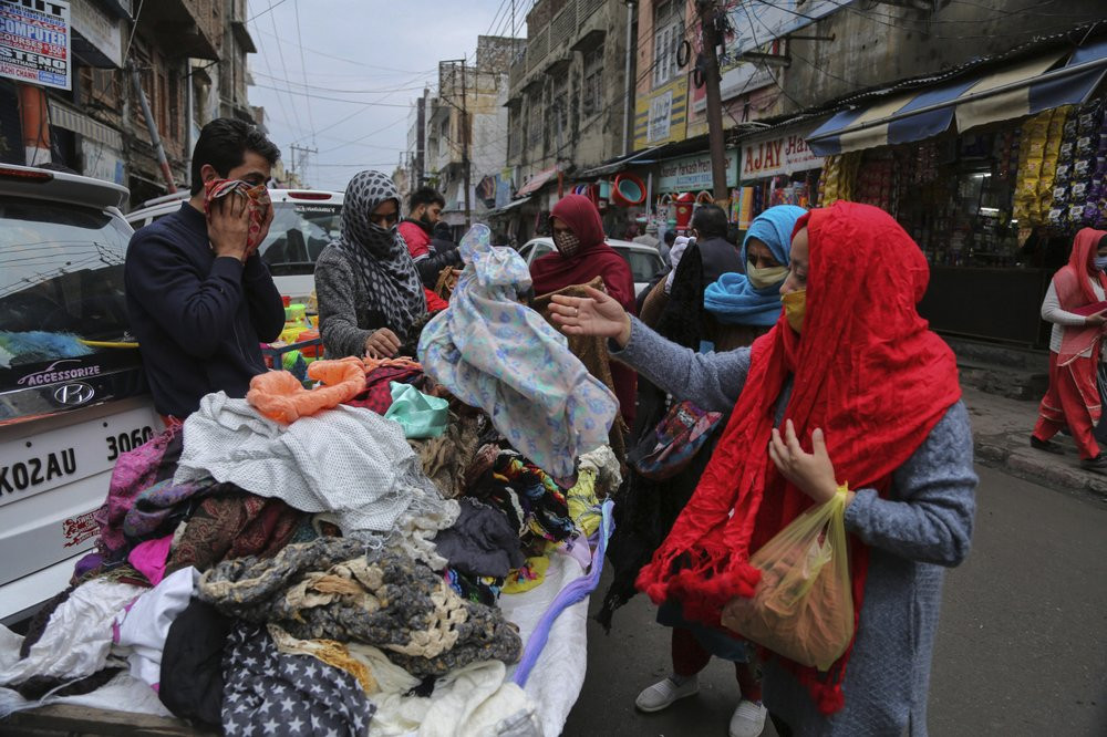Indians, some of them, wearing face masks as a precautionary measure against the coronavirus shop at a Sunday market in Jammu, India, Sunday, Jan.3, 2021.