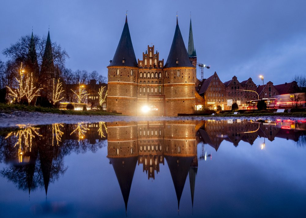 The medieval Holstentor is reflected in water in Luebeck, Germany, Monday, Jan. 4, 2021. The German government will decide about further restrictions to avoid the outspread of coronavirus on Tuesday.