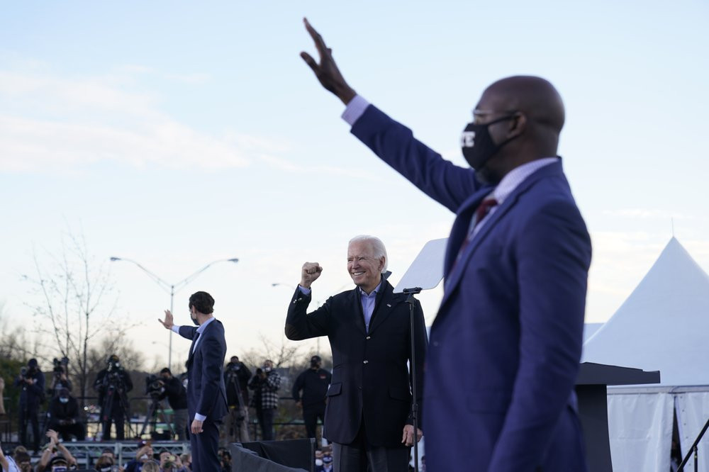 US President-elect Joe Biden campaigns in Atlanta, Monday, Jan. 4, 2021, for Senate candidates Raphael Warnock, right, and Jon Ossoff, left.