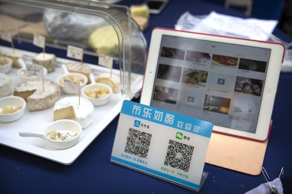 A card displaying QR codes to pay electronically with WeChat Pay and Alipay sits on a vendor's table at a farmer's market in Beijing, Tuesday, Oct. 27, 2020.