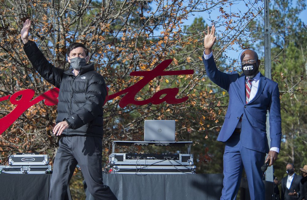Jon Ossoff, left, and Raphael Warnock wave to the crowd during a campaign rally in Augusta, Georgia, Monday, Jan. 4, 2021.