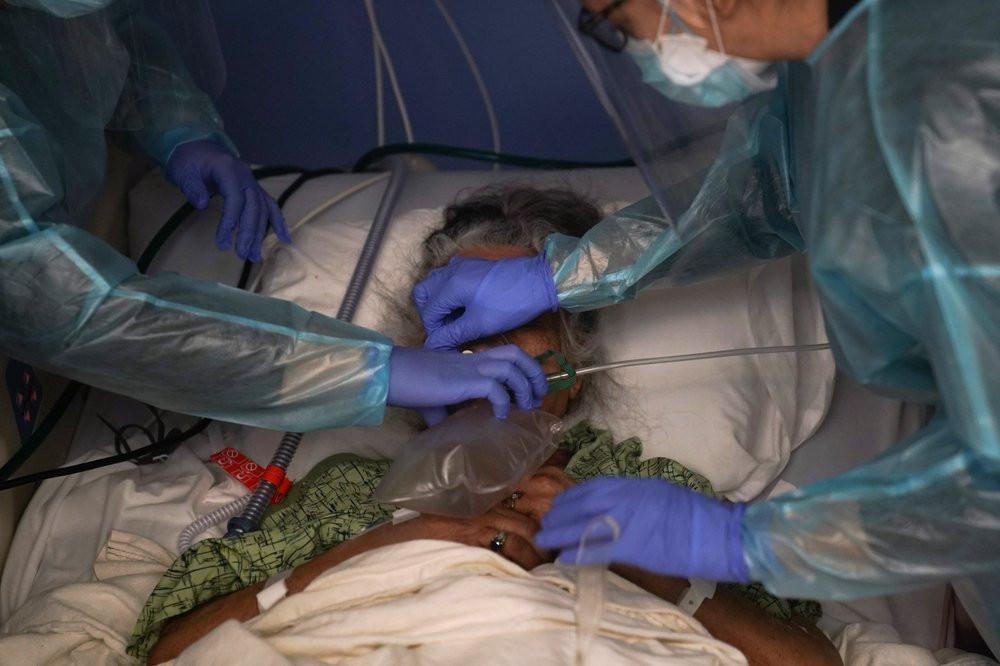 Two nurses put a ventilator on a patient in a COVID-19 unit at St. Joseph Hospital in Orange, Calif. Thursday, Jan. 7, 2021.