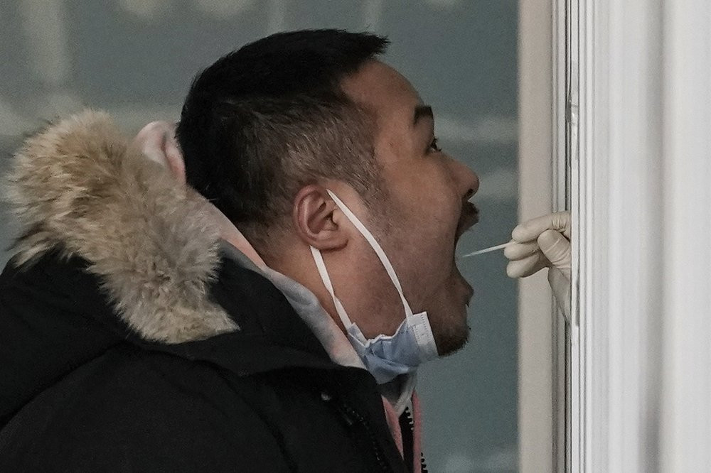 A man gets a swab for the coronavirus test at a hospital in Beijing, Sunday, Jan. 17, 2021.