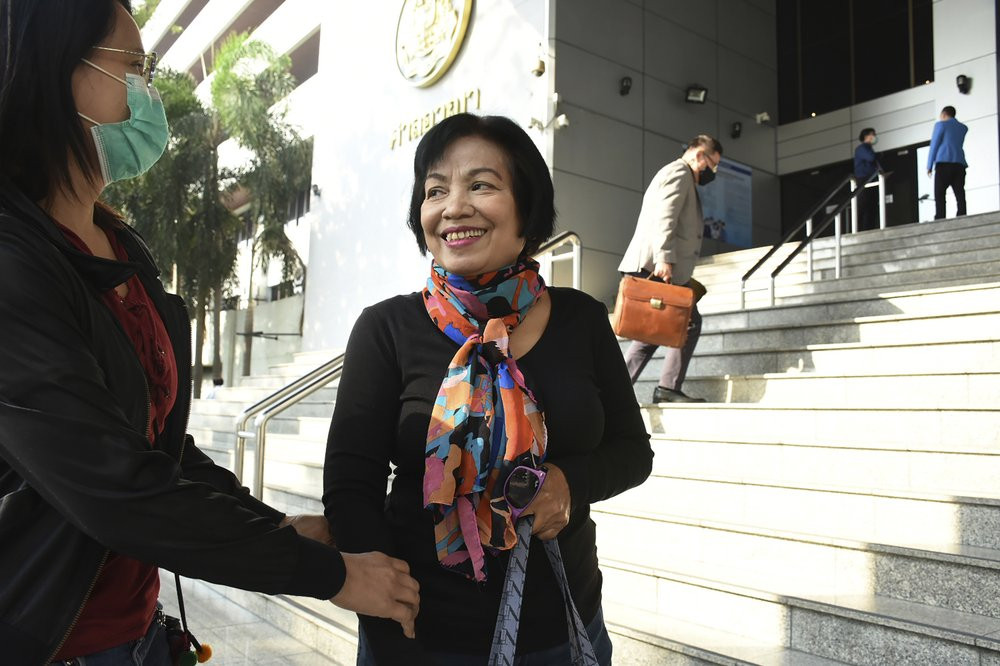 A woman identified only by her first name Anchan, right, talks to her friend as she arrives at the Bangkok Criminal Court in Bangkok, Thailand, Tuesday, Jan. 19, 2021.
