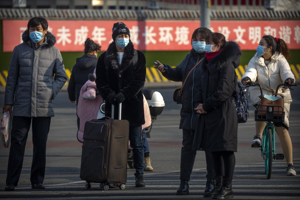 People wearing face masks to protect against the spread of the coronavirus wait to cross an intersection in Beijing, Wednesday, Jan. 20, 2021.