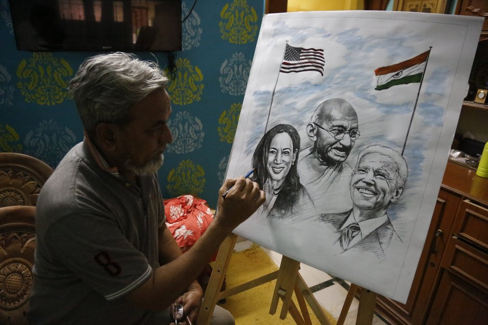 An Indian artist Aejaz Saiyed gives finishing touch to an art work featuring U.S.President-elect Joe Biden, Vice President-elect Kamala Harris and Indian freedom fighter Mahatma Gandhi, ahead of Biden's inauguration ceremony, in Ahmedabad, India.
