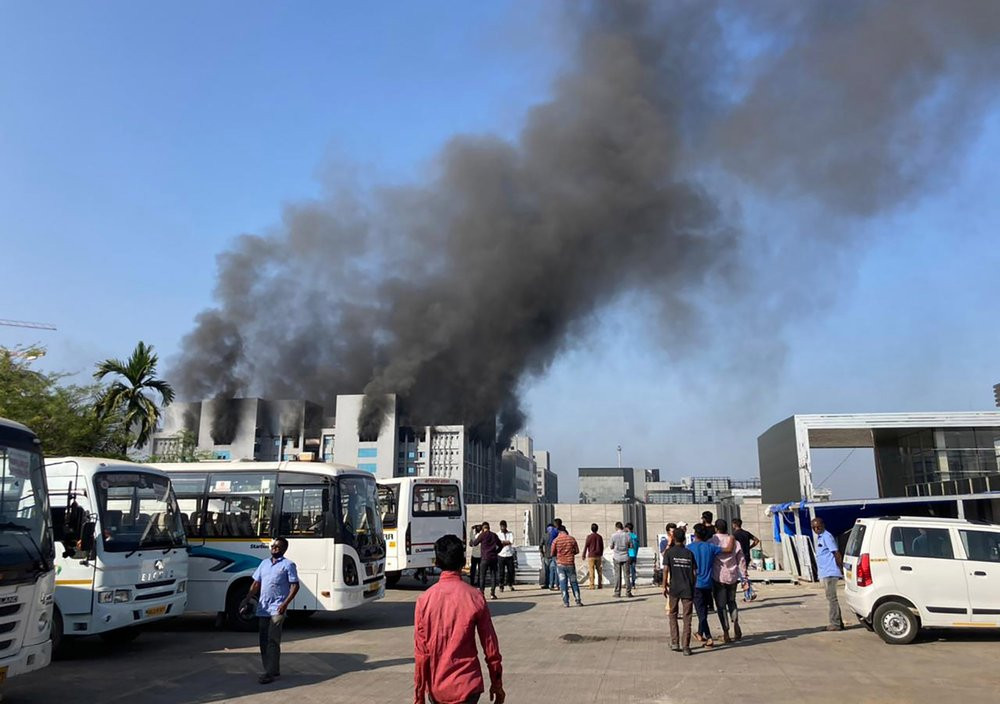 Smoke rises from the Serum Institute of India, the world's largest vaccine maker that is manufacturing the AstraZeneca/Oxford University vaccine for the coronavirus, in Pune, India, Thursday, Jan. 21, 2021.