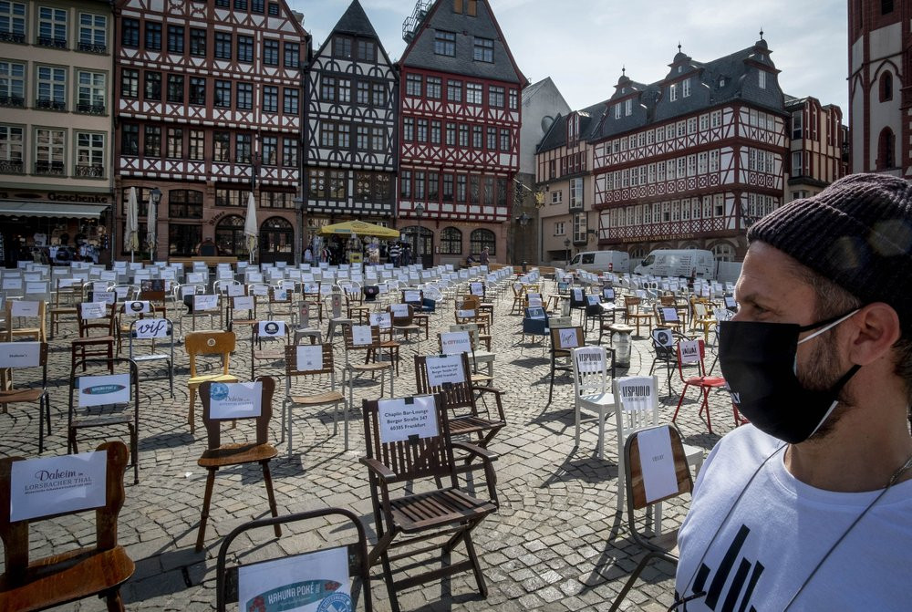 In this April 24, 2020 file photo, a man with a face mask watches empty chairs with names of bars and restaurants on the Roemerberg square in Frankfurt, Germany.