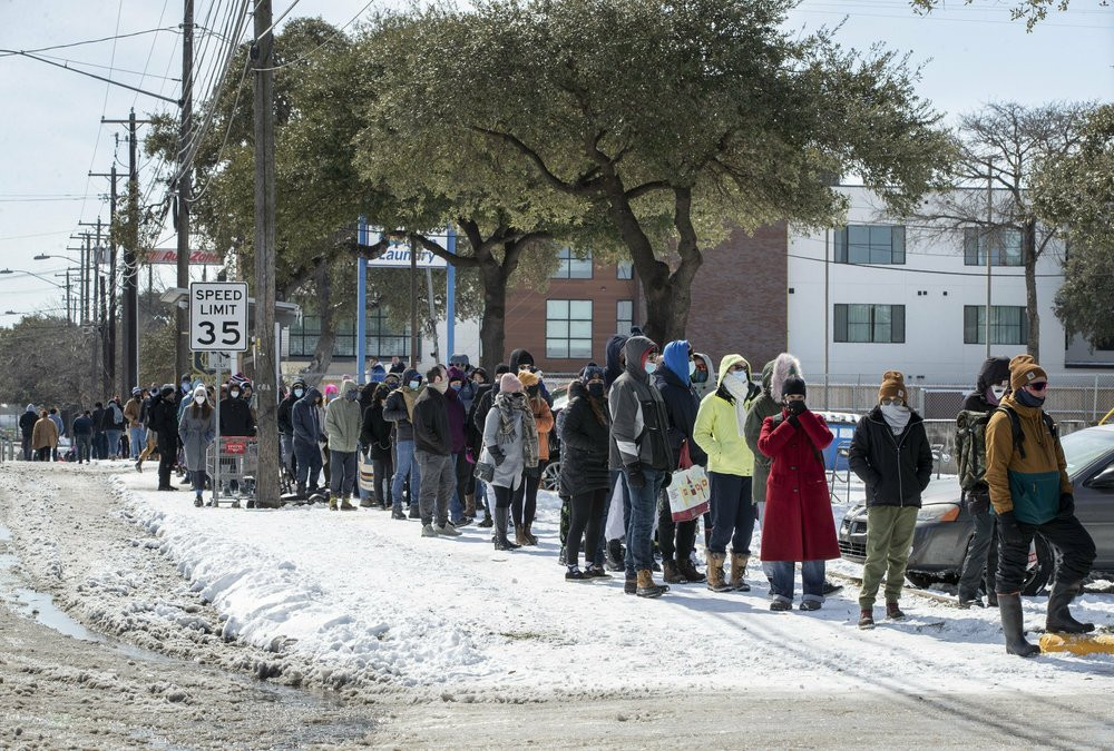 People wait in a long line to buy groceries at H-E-B on South Congress Avenue during an extreme cold snap and widespread power outage on Tuesday, Feb. 16, 2021, in Austin, Texas.