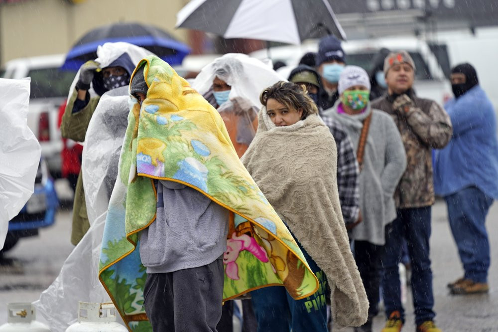 People wait in line to fill propane tanks Wednesday, Feb. 17, 2021, in Houston. Customers waited over an hour in the freezing rain to fill their tanks.