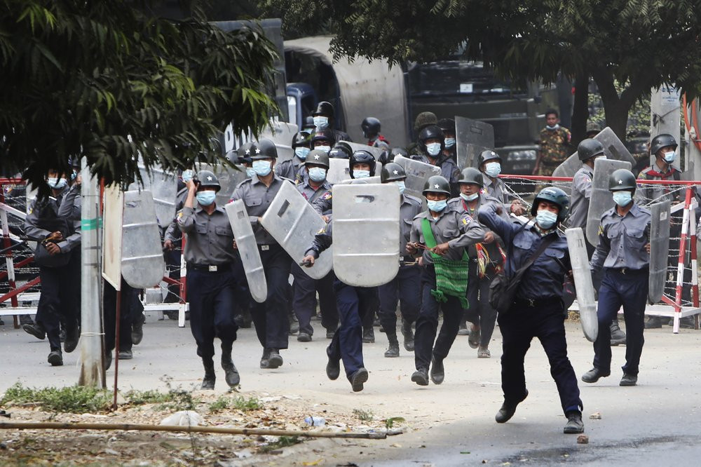 Police charge forward to disperse protesters in Mandalay, Myanmar on Saturday, Feb. 20, 2021.