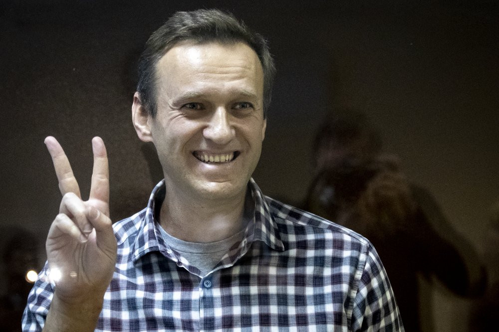 Russian opposition leader Alexei Navalny gestures as he stands behind a grass of the cage in the Babuskinsky District Court in Moscow, Russia, Saturday, Feb. 20, 2021.