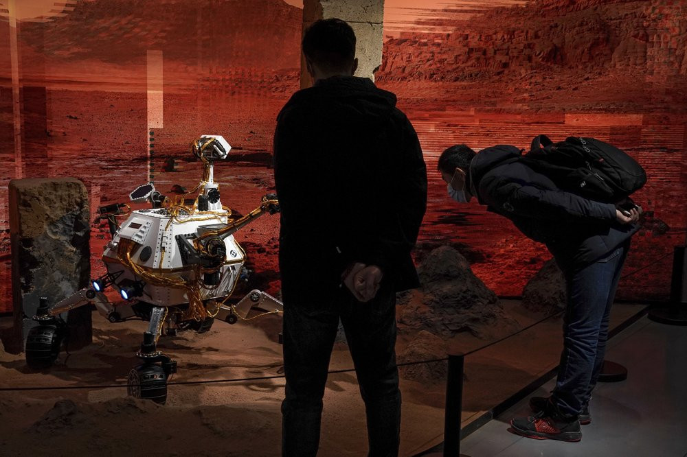 People wearing face masks to help curb the spread of the coronavirus look at a model depicting a rover on Mars during an exhibition at a shopping mall in Beijing on Wednesday, Feb. 24, 2021.