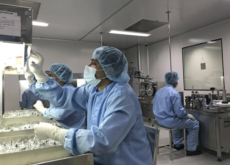 Production personnel perform a visual inspection of filled vaccine vials inside the Incepta plant on the outskirts of Dhaka in Bangladesh Saturday Feb. 13, 2021.
