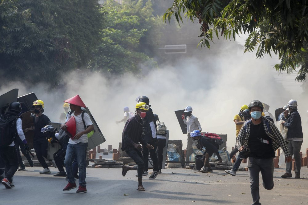 Anti-coup protesters run from teargas and charging riot police and soldiers in Mandalay, Myanmar, Wednesday, March 3, 2021.