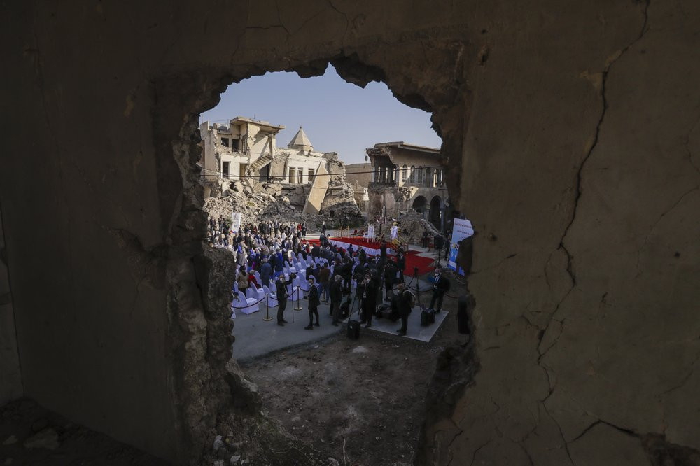 Surrounded by shells of destroyed buildings people arrive to join Pope Francis who will pray for the victims of war at Hosh al-Bieaa Church Square, in Mosul, Iraq, once the de-facto capital of IS, Sunday, March 7, 2021.