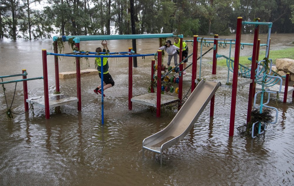 People play on equipment at a playground on the banks of the Nepean River at Jamisontown on the western outskirts of Sydney Monday, March 22, 2021.