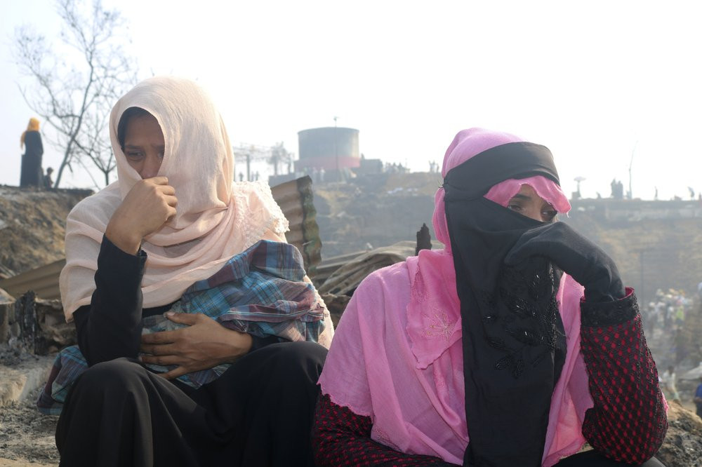Rohingya refugees cry sitting at the site of Monday's fire at a refugee camp in Balukhali, southern Bangladesh, Tuesday, March 23, 2021.