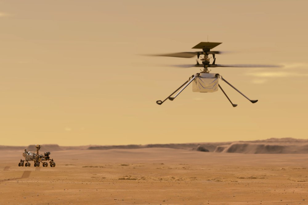 This illustration made available by NASA depicts the Ingenuity helicopter on Mars which was attached to the bottom of the Perseverance rover, background left. It will be the first aircraft to attempt controlled flight on another planet.