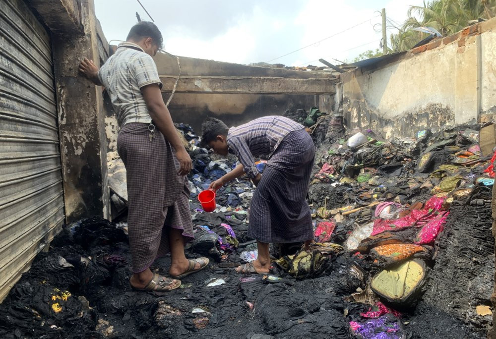 People inspect the debris after a fire in a makeshift market near a Rohingya refugee camp in Kutupalong, Bangladesh, Friday, April 2, 2021.