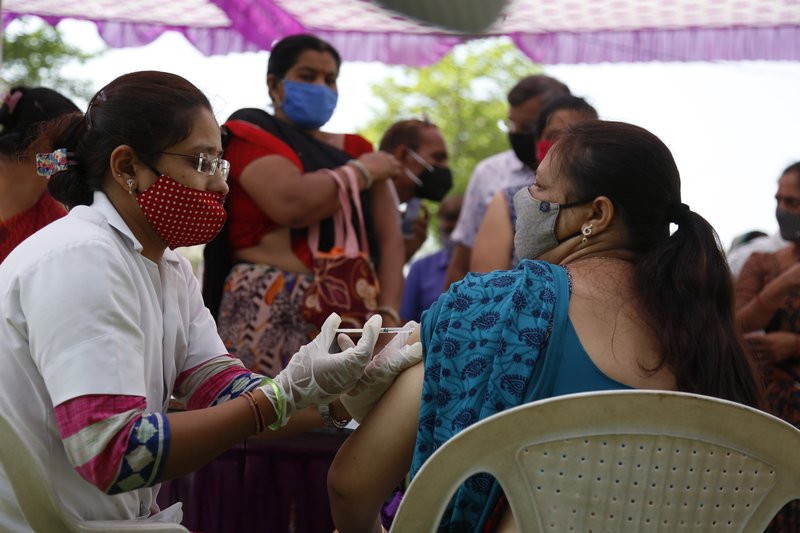 A health worker administers the COVISHIELD vaccine for COVID-19 at a residential area in Ahmedabad, India, Sunday, April 4, 2021.