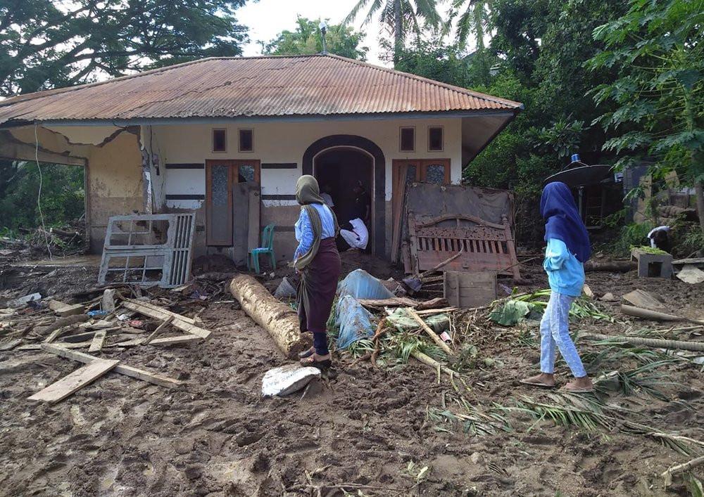 Indonesian women walk past a house damaged by flood in Waiwerang, on Adonara Island, East Nusa Tenggara province, Indonesia, Tuesday, April 6, 2021.