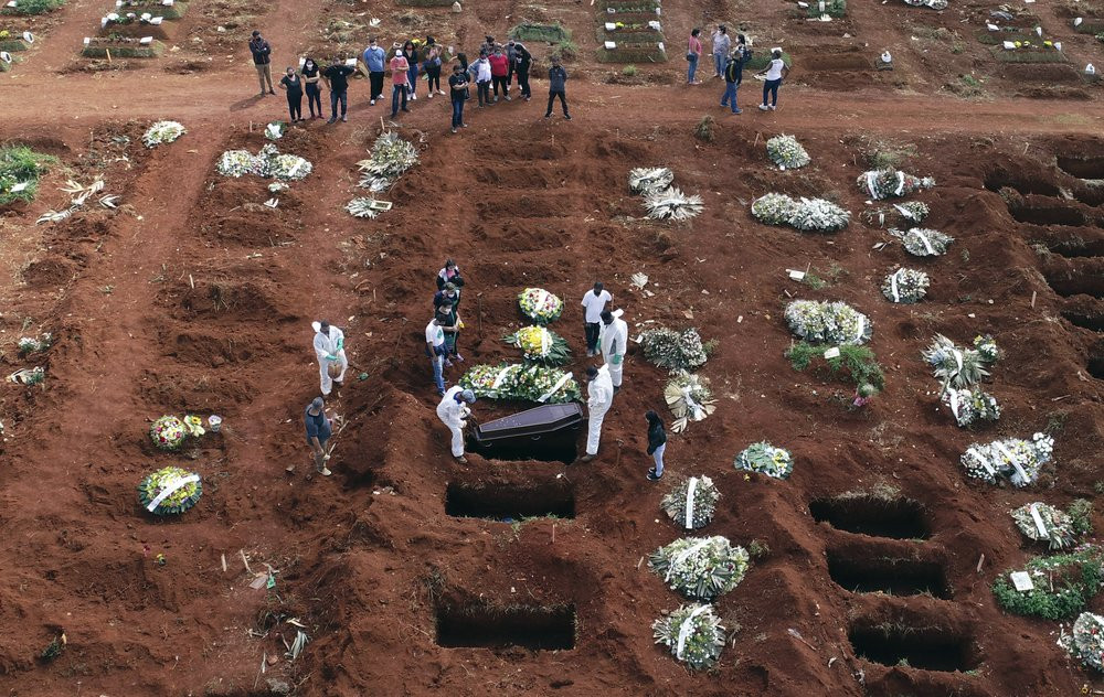 In this April 7, 2021, file photo, cemetery workers wearing protective gear lower the coffin of a person who died from complications related to COVID-19 into a gravesite at the Vila Formosa cemetery in Sao Paulo, Brazil.