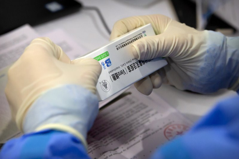 A worker opens a package of coronavirus vaccine made by a Sinopharm subsidiary during a COVID-19 vaccination session for resident foreign journalists at a vaccination center in Beijing, Tuesday, March 23, 2021.