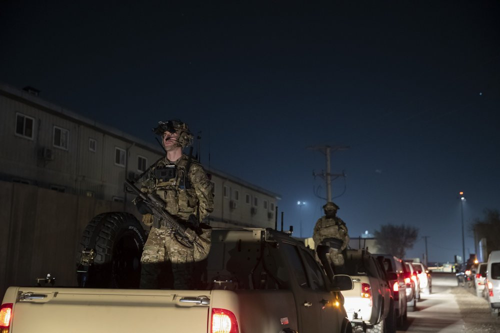 In this Nov. 28, 2019, file photo armed soldiers stand guard in the motorcade for President Donald Trump speaks during a surprise Thanksgiving Day visit to the troops at Bagram Air Field, Afghanistan.