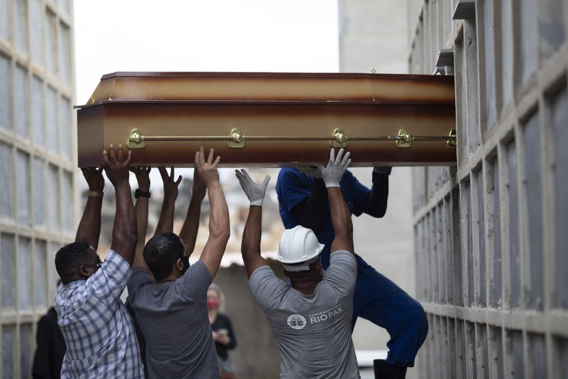 In this April 13, 2021, file photo, the remains of a woman who died from complications related to COVID-19 are placed into a niche by cemetery workers and relatives at the Inahuma cemetery in Rio de Janeiro, Brazil.