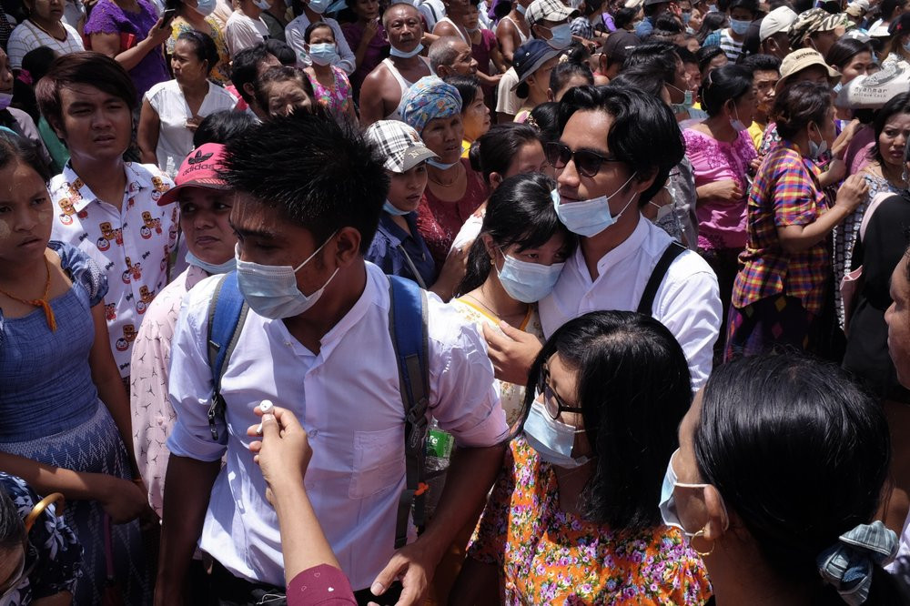 Zay Yar Lwin, center left in white, and Paing Pyo Min,center right in whitewalk through a crowd after their release from Insein prison in Yangon, Myanmar, Saturday, April 17, 2021.