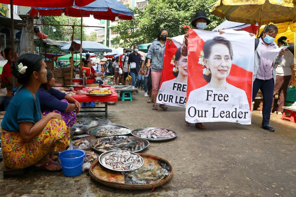 In this April 8, 2021, file photo, anti-coup protesters walk through a market with images of ousted Myanmar leader Aung San Suu Kyi in Yangon, Myanmar.
