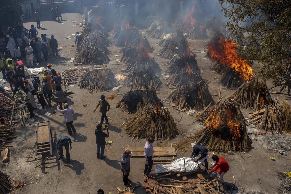 Multiple funeral pyres of victims of COVID-19 burn at a ground that has been converted into a crematorium for mass cremation in New Delhi, India, Saturday, April 24, 2021.