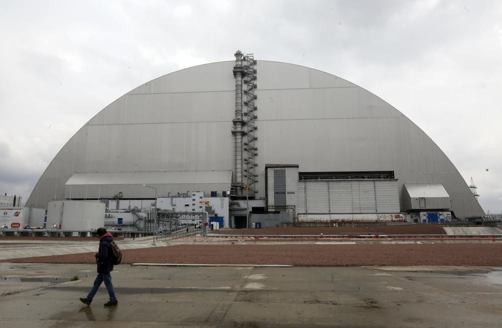 A man walks past a shelter covering the exploded reactor at the Chernobyl nuclear plant, in Chernobyl, Ukraine, Thursday, April 15, 2021.