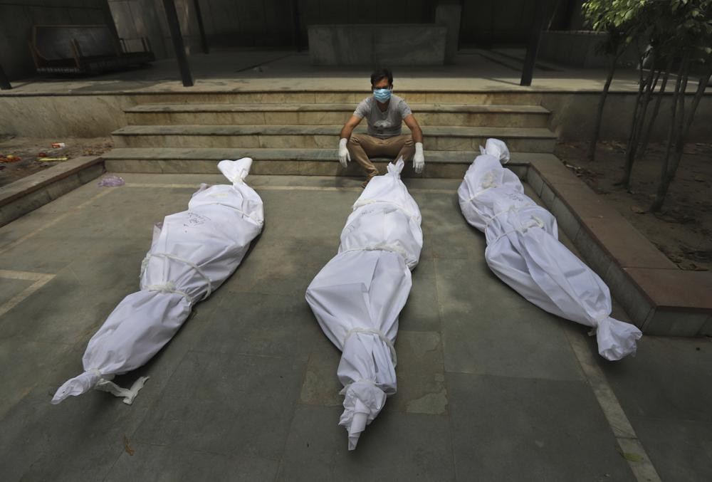 In this April 20, 2021, file photo, a man waits for the cremation of a relative who died of COVID-19, placed near bodies of other victims, in New Delhi, India.