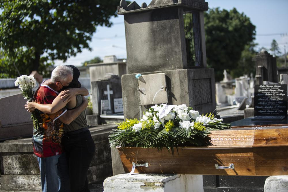 Relatives grieve during the burial service for Monica Cristina, 49, who died from complications related to COVID-19, at the Inahuma cemetery in Rio de Janeiro, Brazil, Wednesday, April 28, 2021.