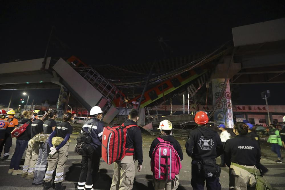 Rescue personnel stand in front of Mexico City subway cars laying at an angle after a section of Line 12 of the subway collapsed in Mexico City, Tuesday, May 4, 2021.