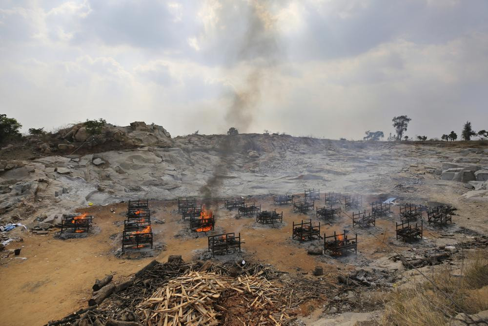 Funeral pyres of twenty-five COVID-19 victims burn at an open crematorium set up at a granite quarry on the outskirts of Bengaluru, India, Wednesday, May 5, 2021.
