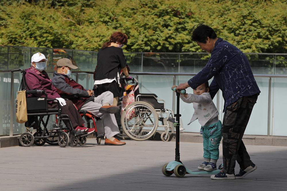 A woman plays with a child near elderly people on wheelchairs sunbathing on a compound of a commercial office building in Beijing on Monday, May 10, 2021.