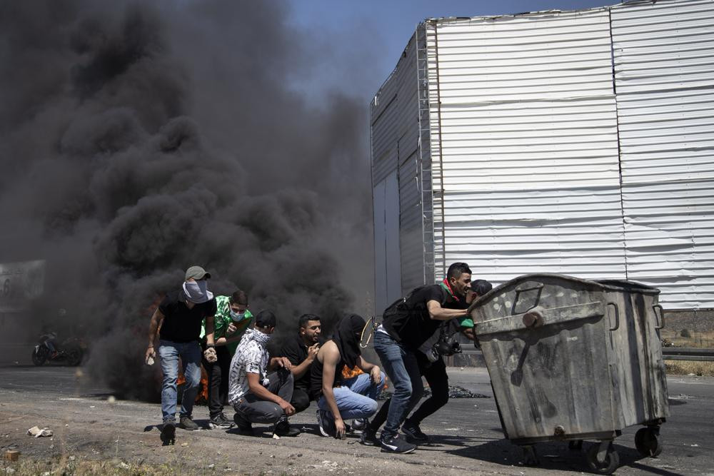 Palestinian demonstrators take cover during clashes with Israeli forces at the Hawara checkpoint, south of the West Bank city of Nablus, Friday, May 14, 2021.