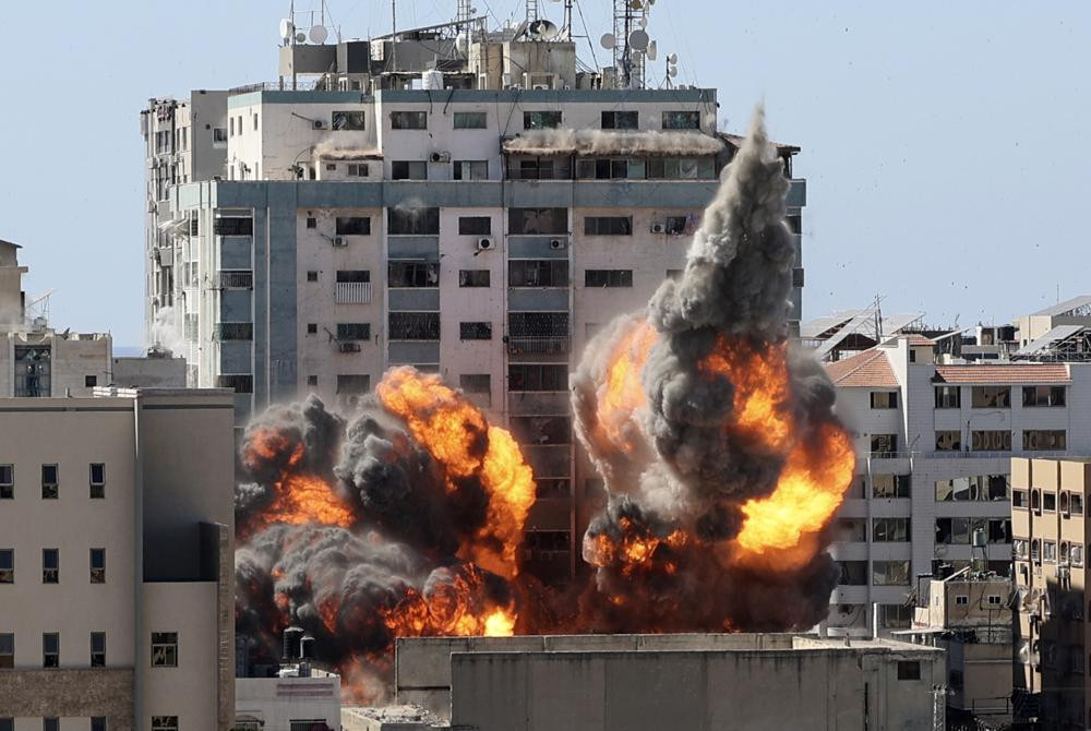 A ball of fire erupts from a building housing various international media, including The Associated Press, after an Israeli airstrike on Saturday, May 15, 2021 in Gaza City.