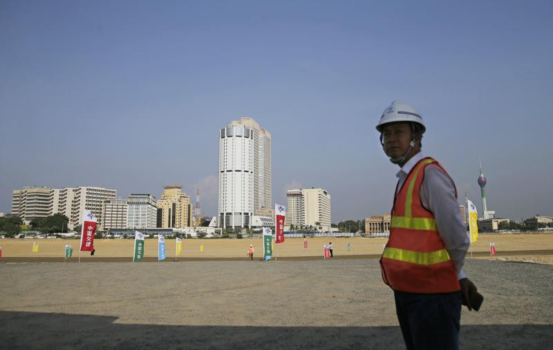 In this Jan. 2, 2018, file photo, a Chinese construction worker stands on land that was reclaimed from the Indian Ocean for the Colombo Port City project, initiated as part of China's ambitious One Belt One Road initiative, in Colombo.