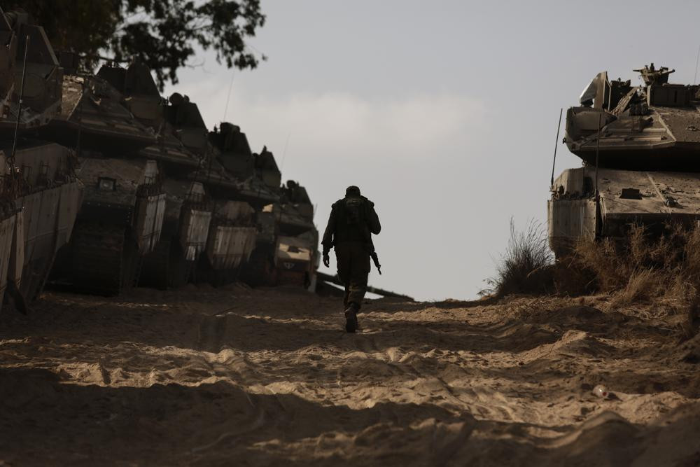 An Israeli soldier walks at a staging ground near the border with the Gaza Strip, in southern Israel, Thursday, May 20, 2021.