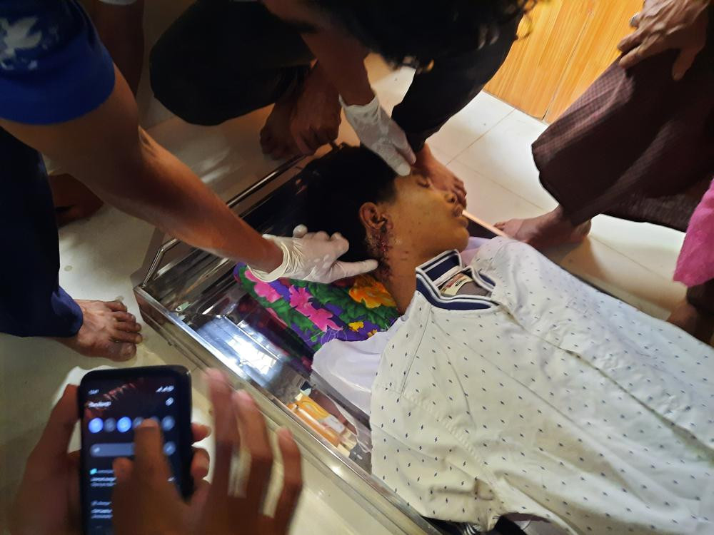 In this March 30, 2021 photo provided by Dawei Watch news outlet, a relative points to an open wound in the neck of 17-year old Kyaw Min Latt in Dawei, Myanmar.
