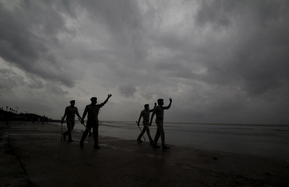 Policemen ask people to move to cyclone shelters as they patrol a beach in Balasore district in Odisha, India, Tuesday, May 25, 2021.