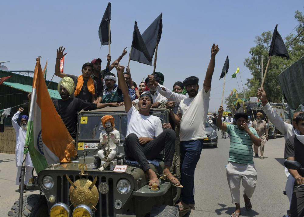 Farmers, some carrying black flags, on a vehicle during a protest in Ghazipur, outskirts of New Delhi, India, Wednesday, May 26, 2021.